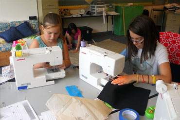 Children learning to use sewing machines at summer camp