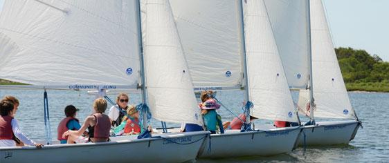 Children enjoying sailing instruction at summer sailing camp